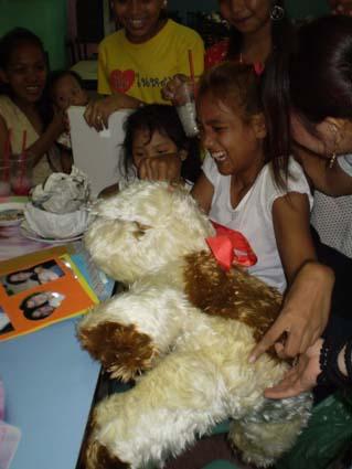 Monthita offrant une peluche à une jeune handicapée physique avec les membres de l'association Points-Cœur